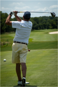 A golfer at the 2014 Golf Challenge, swinging in support of Mercy.